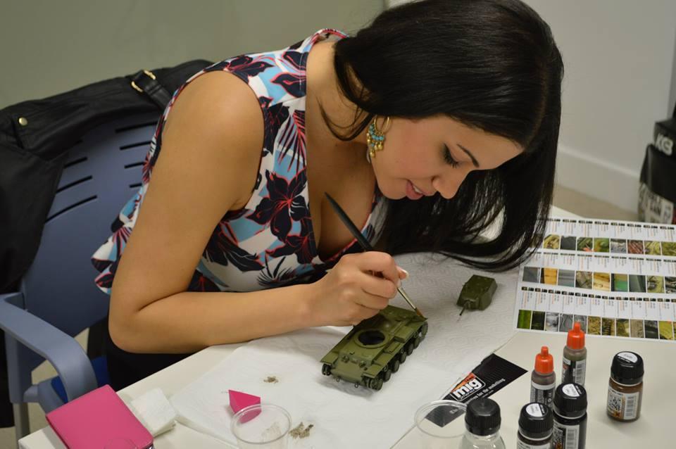 Chica pintando la maqueta de un tanque